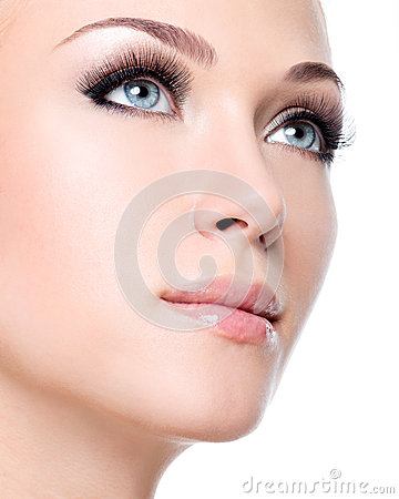 Portrait of beautiful white woman with long false eyelashes