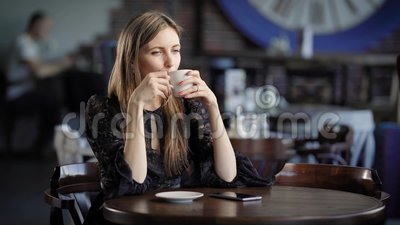 Portrait of a beautiful woman in a cafe or restaurant. A girl drinks tea or coffee and dreams about something. Modern interior of cafe stock footage