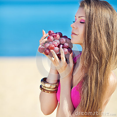 Portrait of beautiful woman with grapes in hands in summer outdoor