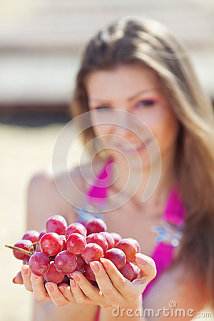 Portrait of beautiful woman with grapes in hands i
