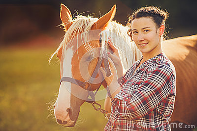 Portrait beautiful woman next horse in warm summer sunny day