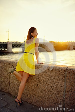 Portrait of the beautiful woman in a yellow dress on the embankment in Sankt Petersburg at sunset
