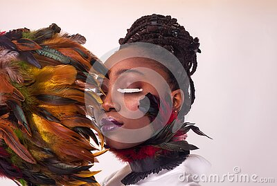 Portrait of a beautiful African woman. Studio with white background. Make up with lashes made of feathers. Fashion style Stock Photo