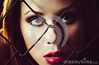 Portrait of beautiful young girl behind the metallic grid. Closeup