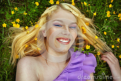 Portrait of beautiful young girl on green grass in the summer