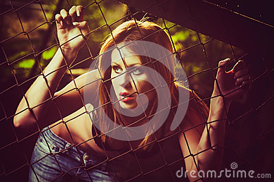 Portrait of beautiful young girl standing behind metallic fence