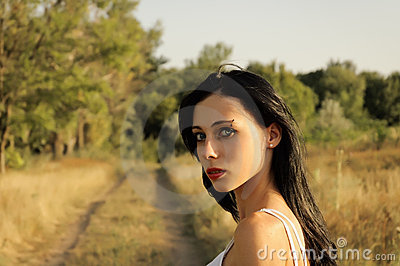 Portrait of a beautiful young girl at sunset