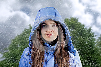 Portrait of beautiful young girl wearing aincoat with hood in a