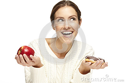 Portrait of a beautiful young woman, choosing between apple and donut Stock Photo