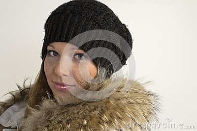 Portrait of beautiful young woman in hat and fur