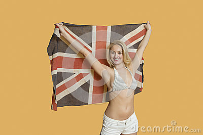 Portrait of a beautiful young woman holding British flag with arms raised over colored background