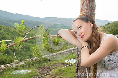 Portrait of beautiful young woman near tree