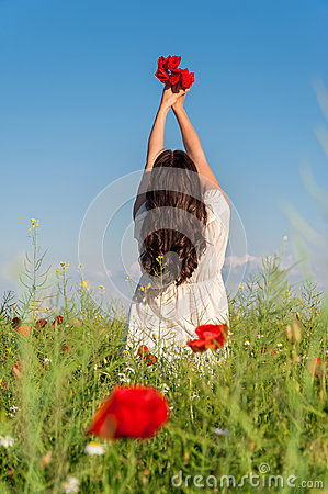 Portrait of beautiful young woman with poppies in the field with a poppies bouquet.Young girl on a poppy field,back view, summer o
