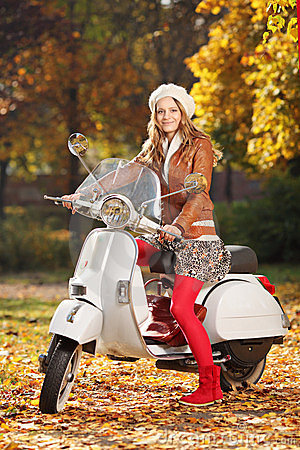 Portrait of beautiful young woman on scooter