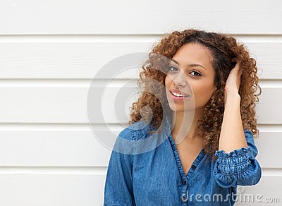 Portrait of a beautiful young woman smiling with hand in hair
