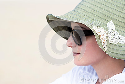 Portrait of a beautiful young woman in sunglasses and green hat