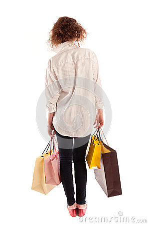 Portrait of a beautiful young woman walking away with shopping