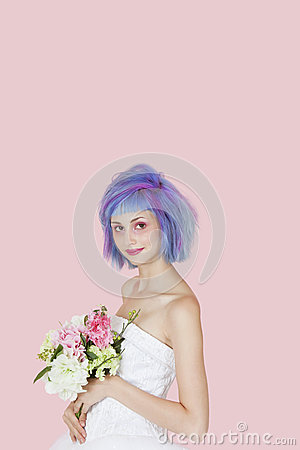 Portrait of beautiful young woman in wedding dress with dyed hair against pink background