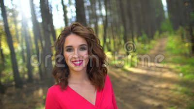 Portrait of Beauty Girl in red dress with Healthy Long Hair in forest. Happy woman smilling and laughing in Autumn in. The sunny fall park outdoor. Nature. slow stock video