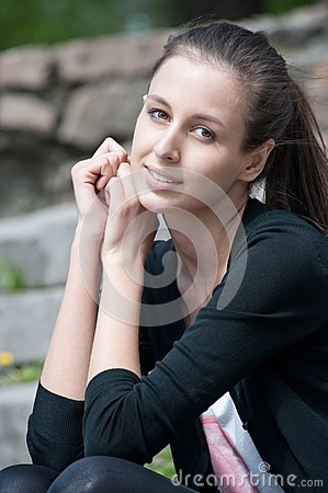 Portrait of beutiful young woman sitting outdoors