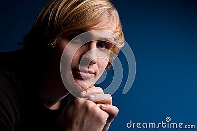 Portrait of blond man over blue background