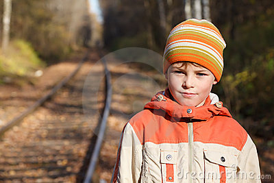 Portrait of boy autumn sunny day on railway