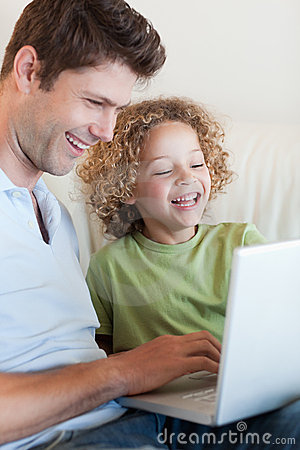 Portrait of a boy and his father using a laptop