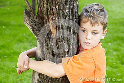 Portrait of boy, that stands hugging tree