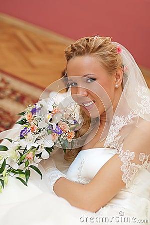 Portrait of bride with bouquet in hands indoors