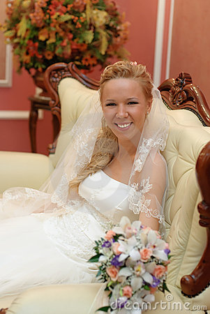 Portrait of bride with bouquet in hands indoors
