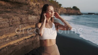 Portrait Brunette Frau in Sportbekleidung auf schwarzem Strand, sieht Kamera stock video