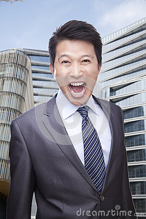 Portrait of Businessman Shouting and Looking At Camera, Buildings in the Background
