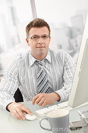 Portrait of businessman using desktop computer