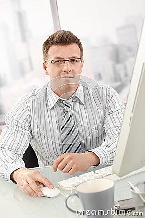 Portrait of businessman using desktop computer