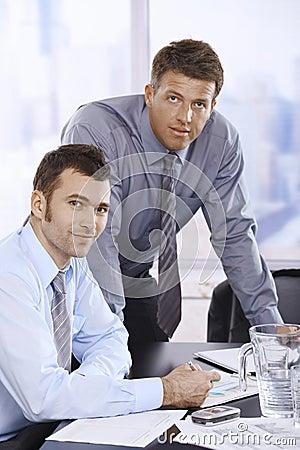 Portrait of businessmen at desk