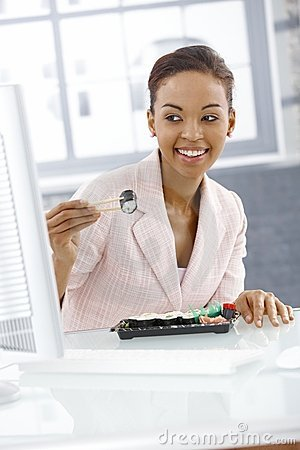Portrait of businesswoman eating sushi