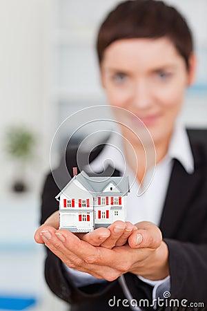Portrait of a businesswoman holding a miniature
