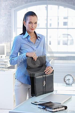 Portrait of businesswoman opening briefcase