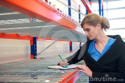 Portrait of a businesswoman writing on clipboard in warehouse