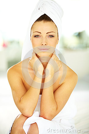 Portrait of a calm young woman wrapped in a towel