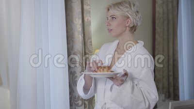Portrait of charming blond Caucasian woman in bathrobe smelling and biting fresh delicious croissant in the morning. Gorgeous lady having breakfast at home or stock video footage