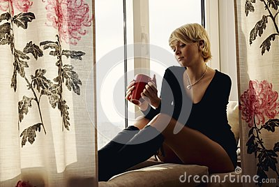Portrait of charming girl sitting on windowsill an