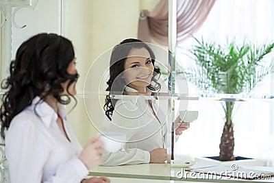 Portrait of cheerful brunette looking in mirror