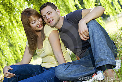 Portrait of cheerful couple sitting under the tree