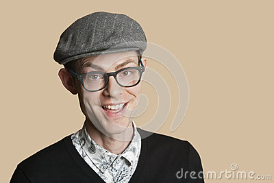 Portrait of a cheerful mid adult man wearing retro glasses over colored background