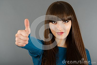 Portrait Of Cheerful Young Woman Gesturing Okay Sign on a gray