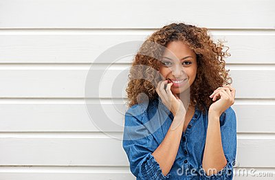 Portrait of a cheerful young woman posing with hand in hair