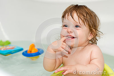 Portrait of cheery cute baby girl in a bath