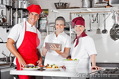Happy Chefs Using Tablet Computer In Kitchen