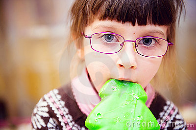 Portrait of child girl biting gingerbread